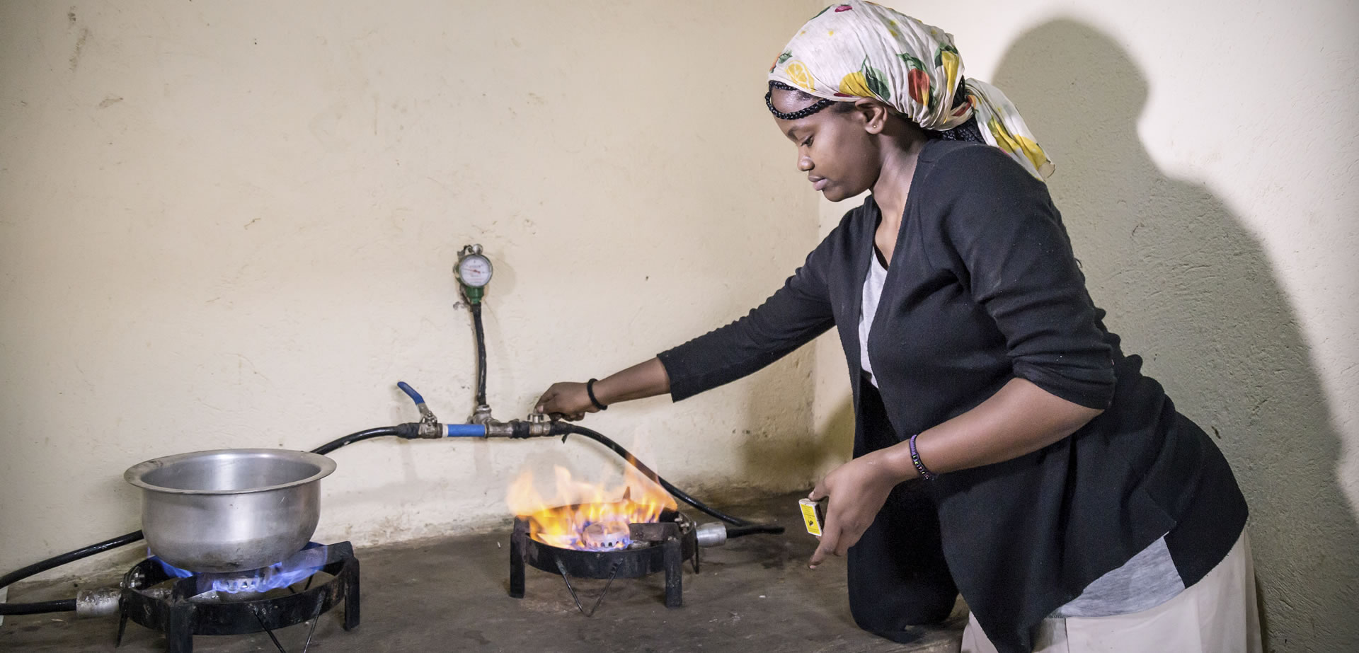 A lady in Uganda using biogas to cook