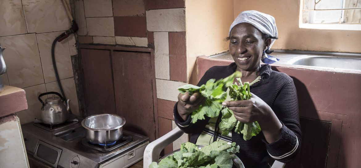 A lady in her kitchen using biogas to cook