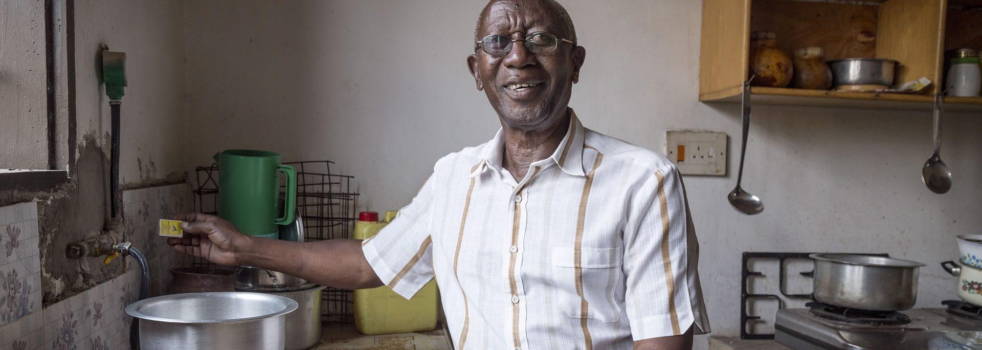 A man lighting a biogas stove in Uganda