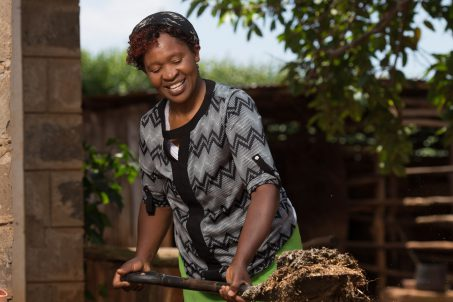 Lady filling biogas biodigester