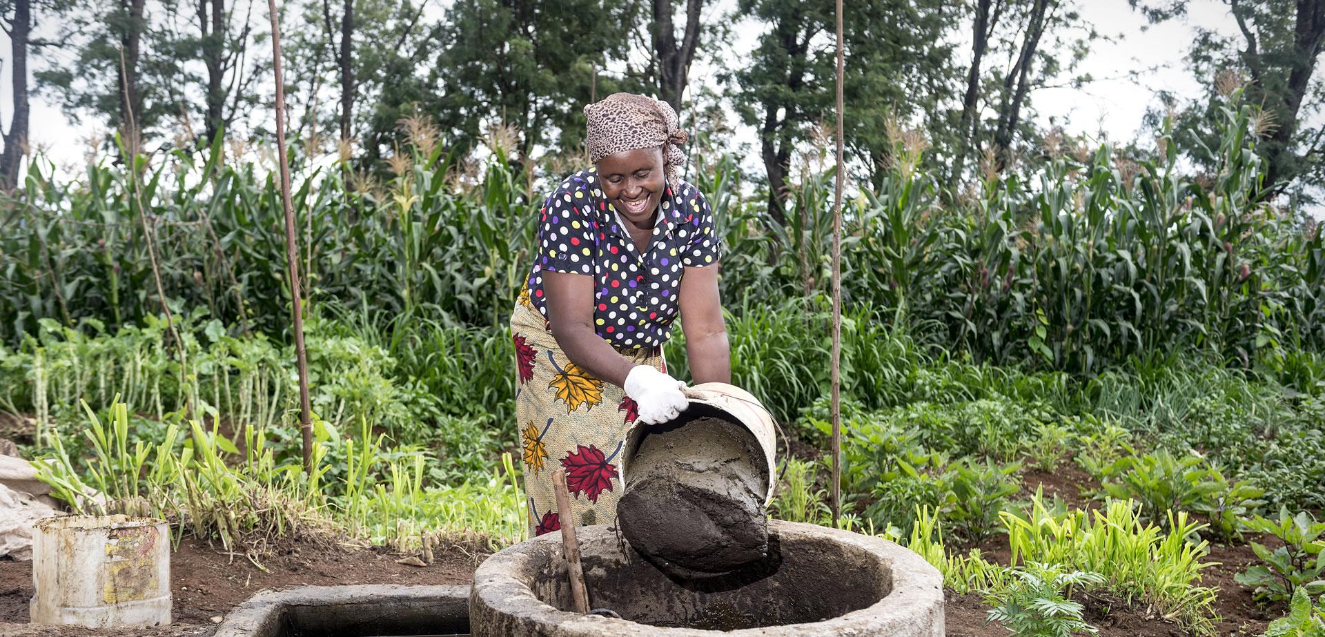 Woman in Tanzania filling a biodigester