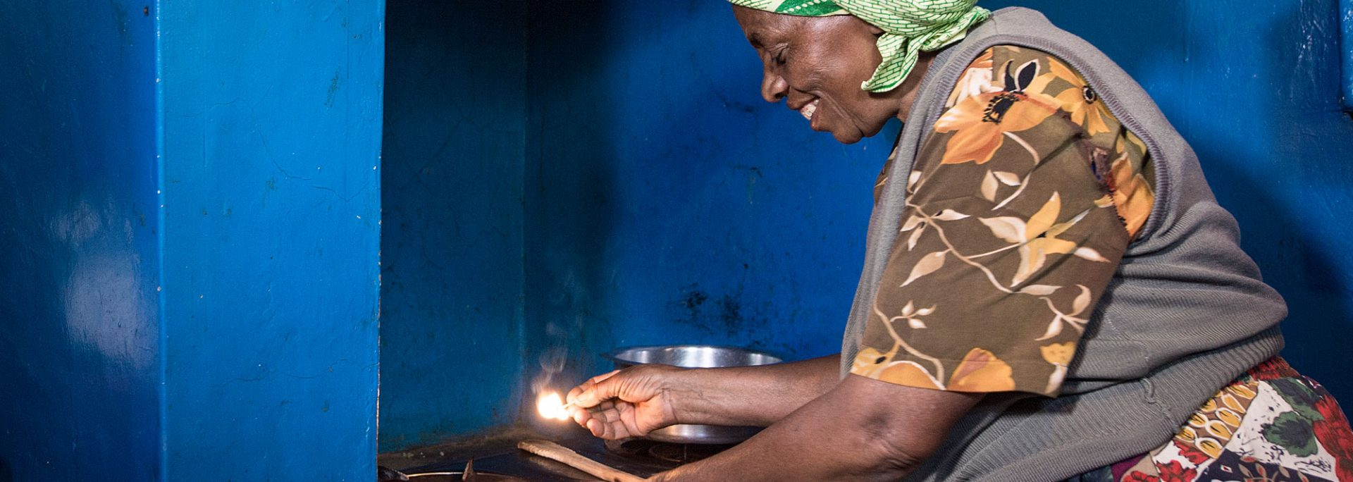 happy lady using biogas to cook